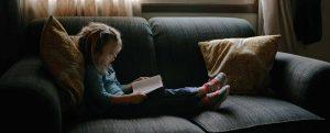 niña leyendo un libro de Prehistoria para niños en un sofá
